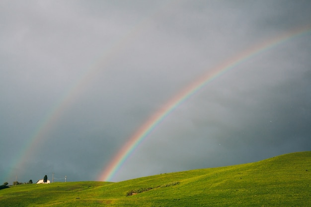 Double rainbow on sky background and green hills