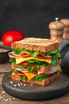 갈색 배경에 치즈 햄과 신선한 야채를 곁들인 더블 샌드위치