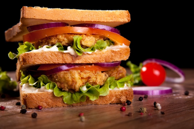 Double sandwich, with chicken, lettuce, tomato, onion, pepper and sauce, on a wooden table and black background.