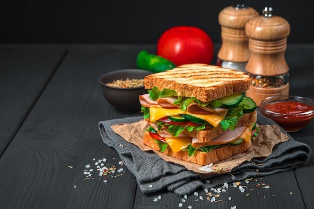 복사 공간이 있는 어두운 배경에 구운 토스트 햄 야채와 치즈를 곁들인 더블 샌드위치