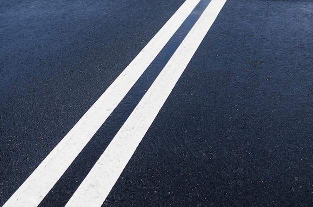 Double solid white line on wet asphalt.