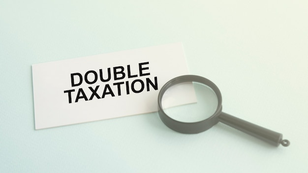Double taxation word on white paper card and magnifying lens