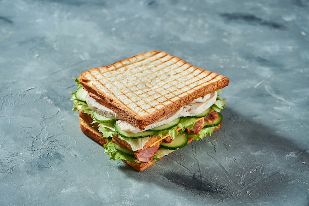 Double toast with chicken, cucumbers and bacon on gray background. selective focus on tasty sandwich