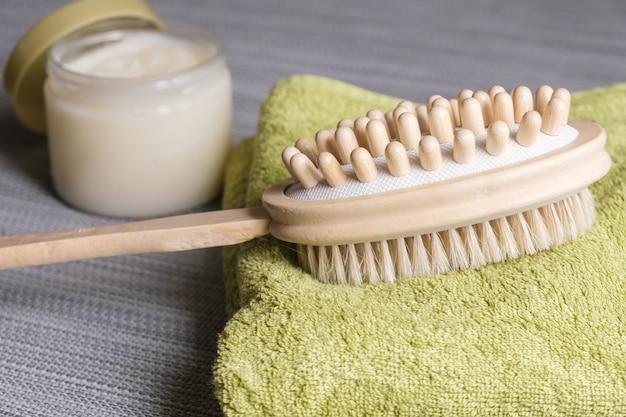 바디 브러싱을 위한 양면 마사지 브러시는 배경 바디 스크럽의 수건에 놓여 있습니다.