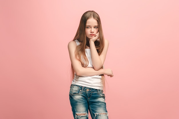 Doubt concept. doubtful, thoughtful sad teen girl remembering something. human emotions, facial expression concept. teenager posing at studio on pink background