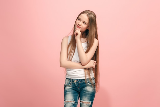 Doubt concept. doubtful, thoughtful teen girl remembering something. human emotions, facial expression concept. teenager posing at  on pink wall