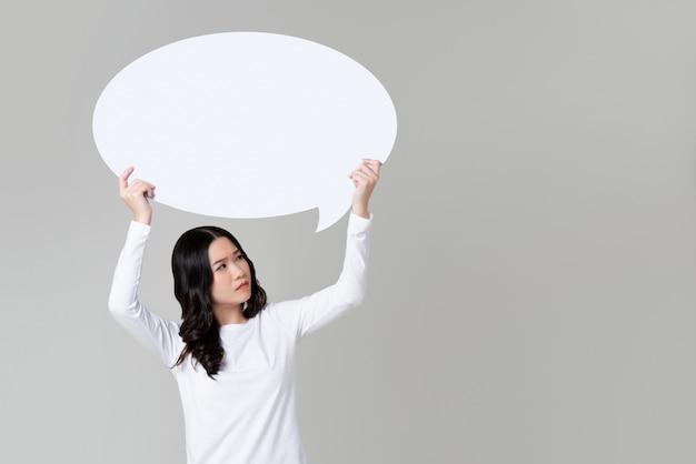 Doubted asian woman raising speech bubble