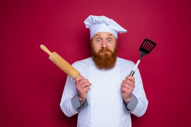 수염과 빨간 앞치마 요리사가 나무 롤링 핀을 들고 의심하는 요리사