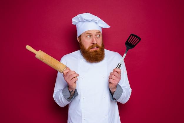 수염과 빨간 앞치마 요리사가 나무 롤링 핀을 들고 의심스러운 요리사