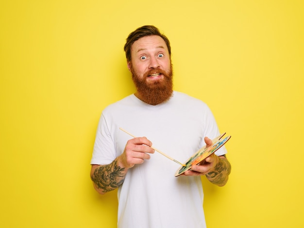 Doubter man with beard and tattoo is ready to draw with brushes