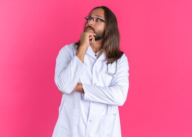 의료 가운과 청진기를 착용한 의심스러운 성인 남성 의사가 턱에 손을 대고 복사 공간이 있는 분홍색 벽에 격리된 모습