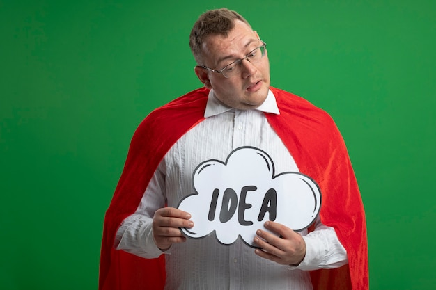 Сомнительный взрослый славянский супергерой в красном плаще в очках, держащий и смотрящий на пузырь идеи, изолированный на зеленой стене с копией пространства