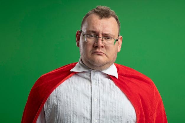 緑の壁に隔離された眼鏡をかけている赤いマントの疑わしい大人のスラブのスーパーヒーローの男