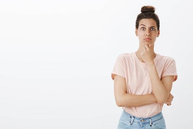 Сомнительная и невежественная молодая стильная женщина позирует у белой стены