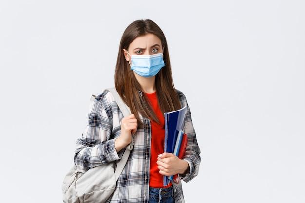 Сомнительная и скептическая студентка в медицинской маске нахмурилась разочарованно, держала блокноты и рюкзак
