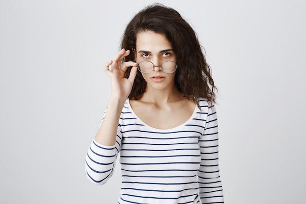 恥ずかしそうに見える疑わしい、懐疑的な若い女性の離陸用メガネ
