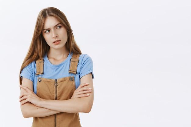 Сомнительная и подозрительная молодая женщина смотрит прямо с неуверенным лицом