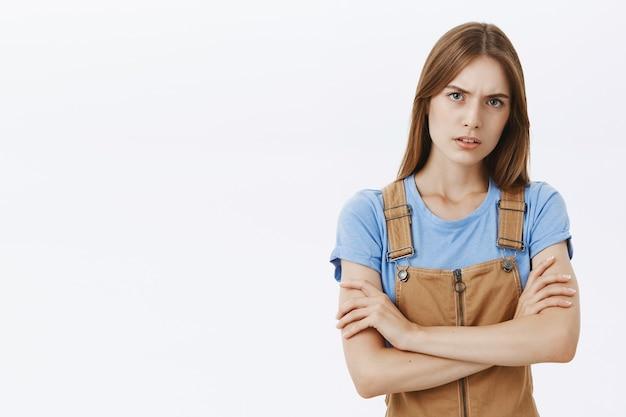 Сомневающаяся и подозрительная молодая женщина смотрит с неуверенным выражением лица