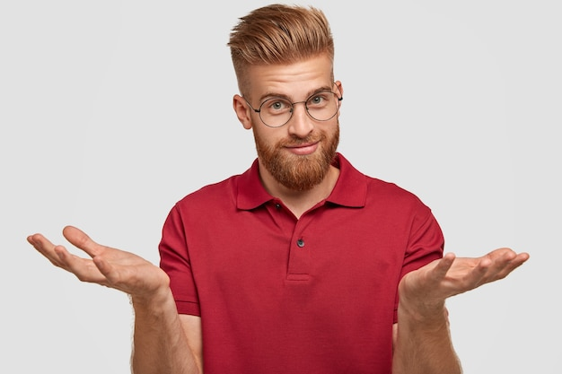 Doubtful attractive bearded young male with ginger hair, thick beard and mustache, shruggs shoulders, doubts what to buy, has appealing look, poses against white wall. hesitation concept