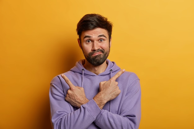Doubtful bearded guy crosses hands and points index fingers at opposite sides, has difficulty in choosing something, purses lips with hesitation, wears hoodie, isolated on yellow wall.
