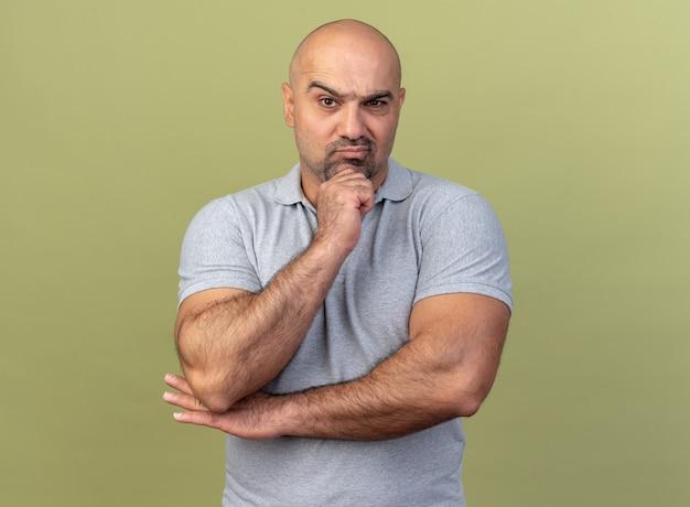 オリーブグリーンの壁に隔離されたあごに手を保持している疑わしいカジュアルな中年男性