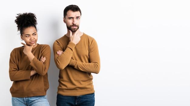 Doubtful couple posing together