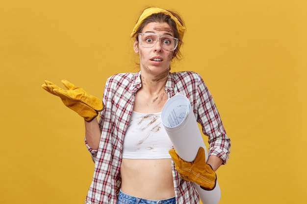 Doubtful female engineer doing manual work shrugging her shoulders with uncertainty. dirty woman with protective eyewear, checkered shirt and yellow gloves holding blueprint.