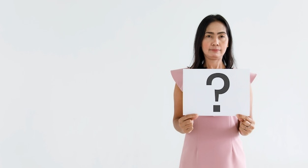 Doubtful female officer staff in business suit look at camera holding big question mark paper cardboard sign showing smile for answers on white background.