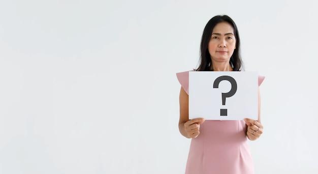 비즈니스 정장을 입은 의심스러운 여성 장교 직원은 배경에 대한 답변에 대한 미소를 보여주는 큰 물음표 종이 판지 기호를 들고 카메라를 봅니다.