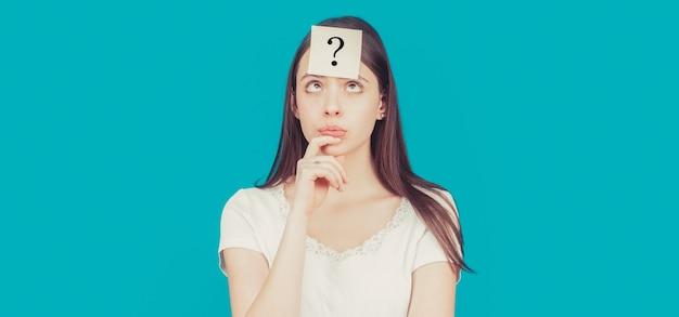 自分に質問をする疑わしい女の子。疑問符の付いた紙のメモ。額の付箋に疑問符が付いた混乱した女性の思考。
