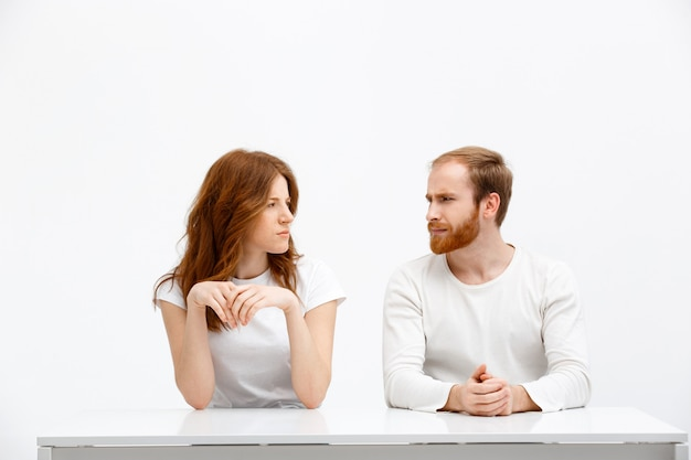 Doubtful girl and man look each other disbelief