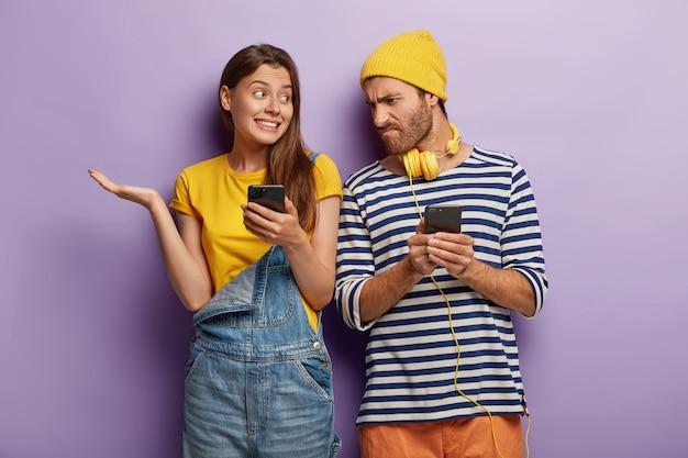 Сомнительно обрадованная европейка и озадаченный парень держит смартфон недовольно хмурится. современные технологии