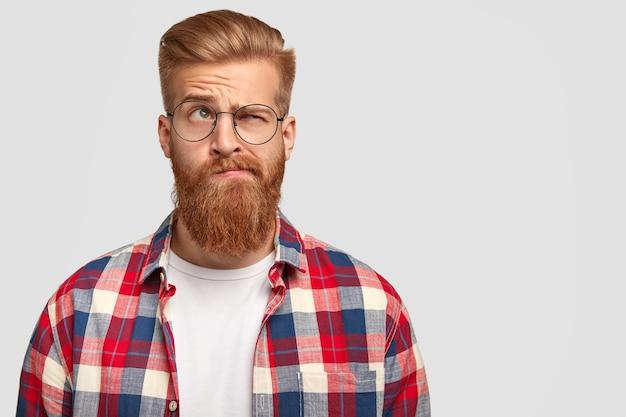 Uomo dubbioso esitante con barba e capelli rossi, chiude un occhio e guarda con espressione incapace