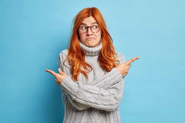 Doubtful hesitant redhead woman crosses arms over body points at different sides or directions and chooses between two options wears knitted sweater.