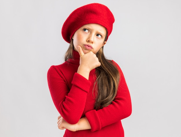 Doubtful little blonde girl wearing red beret keeping hand on chin looking side isolated on white wall with copy space