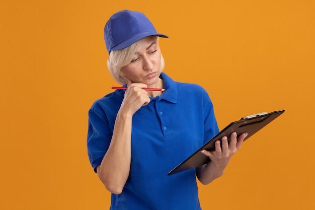 파란색 유니폼을 입은 의심스러운 중년 금발 배달부 여성, 클립보드와 연필을 들고 클립보드를 보고 있는 모자는 복사공간이 있는 주황색 벽에 입술을 오므린 채 턱에 손을 대고 있습니다.