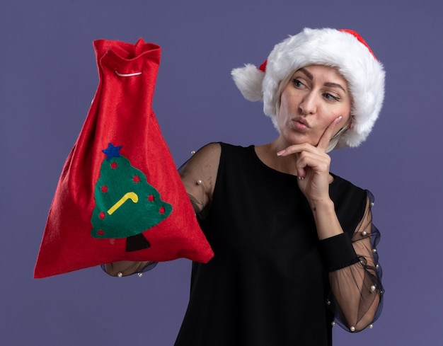 Сомнительная блондинка средних лет в рождественской шляпе, держащая рождественский мешок, смотрит на него, держа руку на подбородке, изолированную на фиолетовом фоне