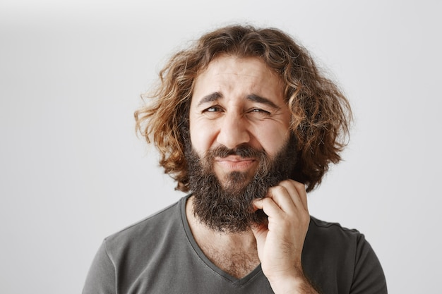 Doubtful middle-eastern guy scratch beard and frowning perplexed