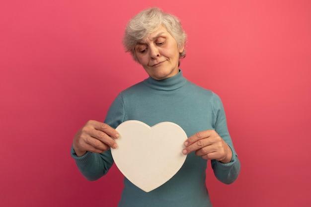 Una donna anziana dubbiosa che indossa un maglione blu a collo alto che tiene e guarda la forma del cuore isolata sul muro rosa