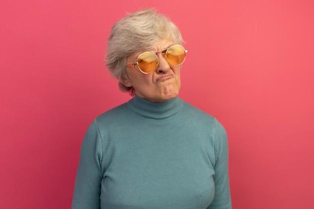 Una donna anziana dubbiosa che indossa un maglione blu a collo alto e occhiali da sole che guarda in alto isolato sul muro rosa con spazio per le copie