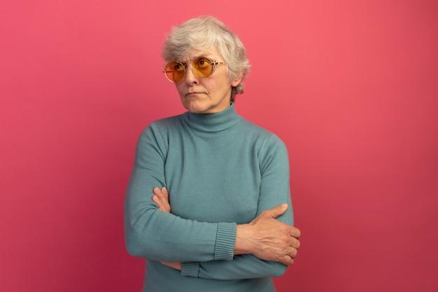 Una donna anziana dubbiosa che indossa un maglione blu a collo alto e occhiali da sole
