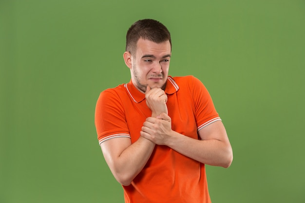Uomo pensieroso dubbioso con l'espressione premurosa che opera scelta contro la parete verde