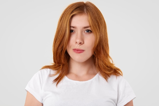 Doubtful pretty female purses lips and looks with hesitation, has reddish hair, dressed in casual t shirt, tries to make choice