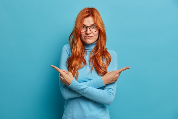 Doubtful redhead woman chooses between two ways crosses arms over body indicates at different sides dressed in casual clothing.