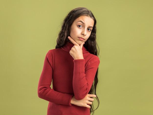 복사 공간이 있는 올리브 녹색 벽에 격리된 카메라를 보고 턱에 손을 대고 있는 의심스러운 10대 소녀