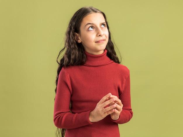 Adolescente dubbioso che tiene le mani insieme guardando in alto isolato sulla parete verde oliva con spazio copia