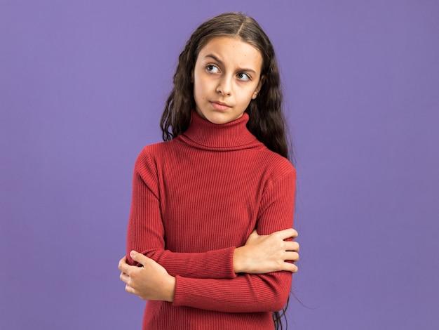 Adolescente dubbioso in piedi con postura chiusa guardando il lato isolato sulla parete viola con spazio copia