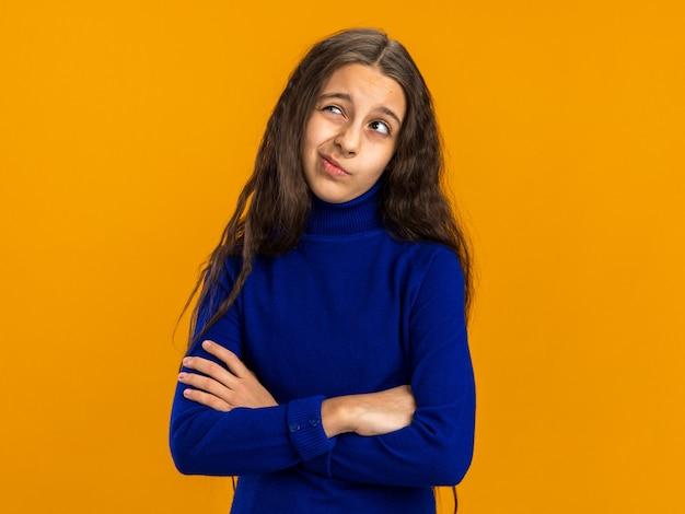 닫힌 자세로 서 있는 의심스러운 10대 소녀가 복사 공간이 있는 주황색 벽에 고립되어 올려다보고 있습니다.