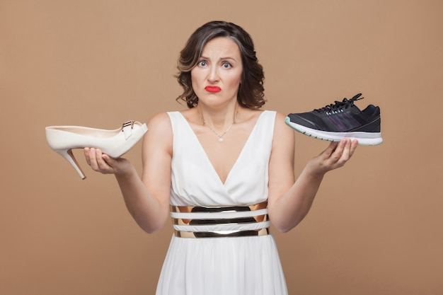 Сомнительно думающая деловая женщина в белом платье стоит, держит элегантные высокие каблуки и удобные кроссовки и не знает, что выбрать. студийный снимок, закрытый, изолированный на светло-коричневом фоне