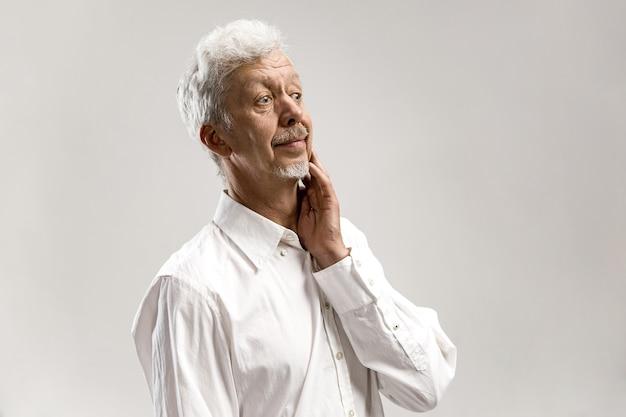 Uomo dubbioso e premuroso che ricorda qualcosa. uomo emotivo senior. emozioni umane, concetto di espressione facciale. isolato su grigio